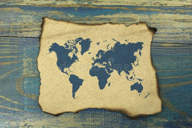 Światowa mapa na burnt papierze na błękitnym starym drewnianym tle zdjęcia stock