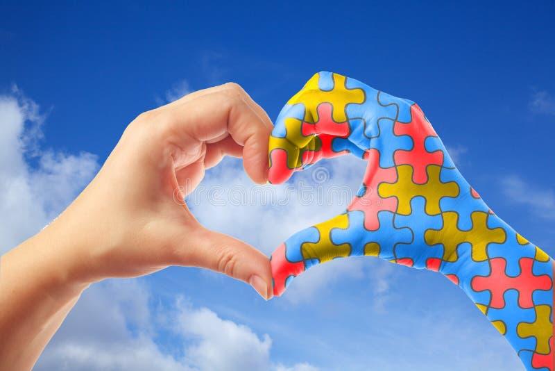 Światowy autyzm świadomości dzień, umysłowy opieki zdrowotnej pojęcie z łamigłówki wyrzynarki wzorem na kierowych kształt rękach zdjęcia royalty free