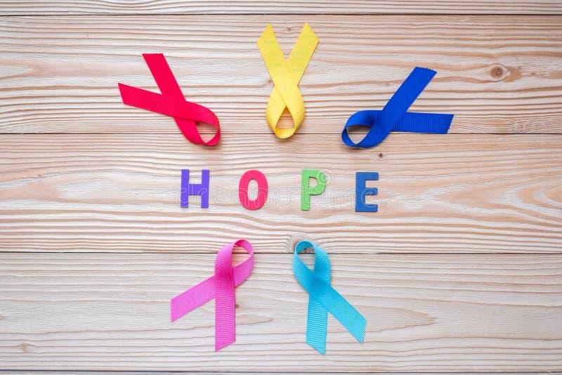 Światowy nowotworu dzień Luty 4 kolorowi świadomość faborki; błękit, czerwień, menchie i żółty kolor na drewnianym tle dla wspier zdjęcie royalty free