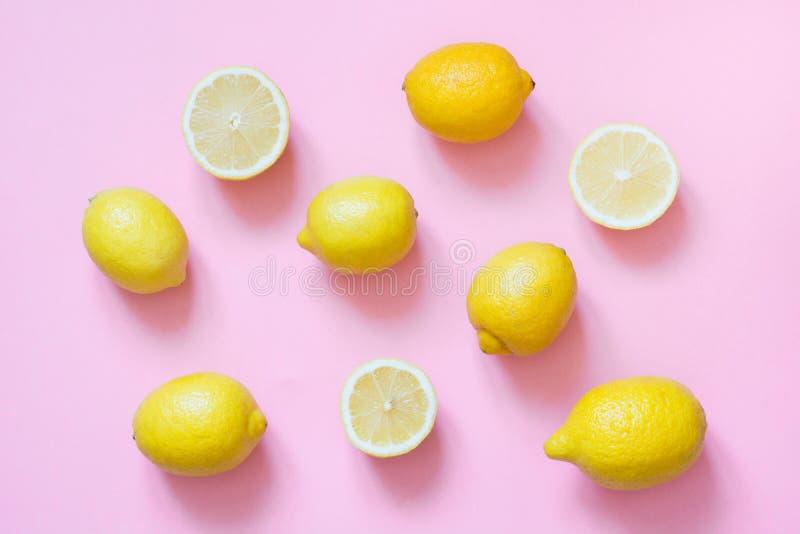 Świeża cała i pokrojona cytryna na różowym tle Mieszkanie nieatutowy zdjęcie stock