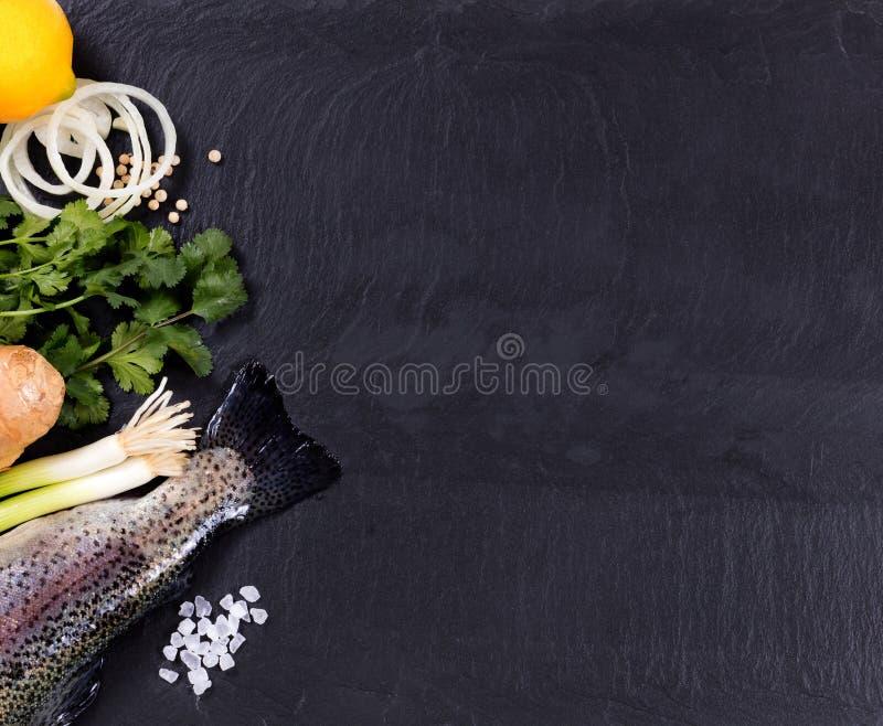 Świeża cała ryba i ziele wystawiający na naturalnym łupku kamieniu z powrotem obraz stock