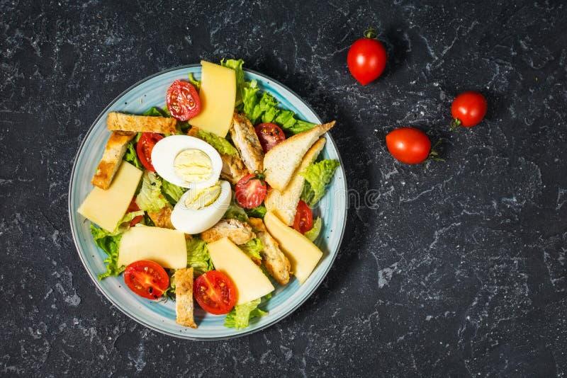 Świeża Caesar sałatka w talerzu na czerń kamienia stole wierzchołek obraz stock