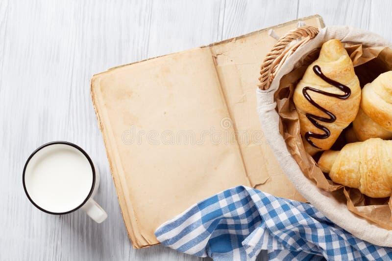 Świeża croissants, dojnej i starej książka, obraz royalty free