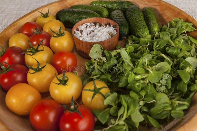 Świeża czerwień, żółci czereśniowi pomidory i ogórki, cebule na drewnianej tacy w wieśniaku projektujemy zdjęcie stock