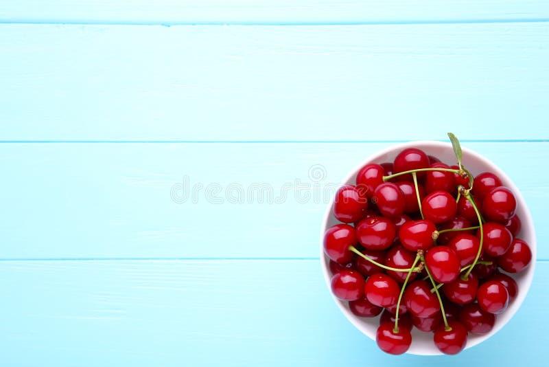 Świeża czerwona czereśniowa owoc w talerzu na błękitnym drewnianym stole zdjęcia stock