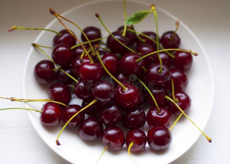 Świeża czerwona czereśniowa owoc w talerzu na drewno stołu tle obraz stock