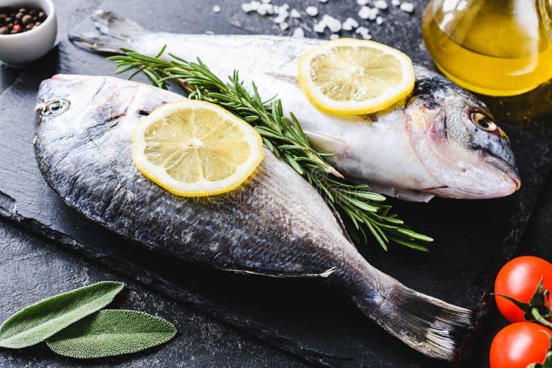 Świeża denna ryba na łupek desce przygotowywającej dla gotować obrazy stock