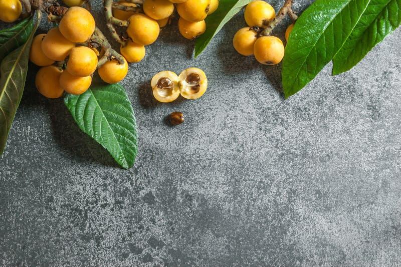 Świeża dojrzała loquat japońskiego niesplika owoc z gałąź i liściem na popielatym wieśniaka stole zdjęcia royalty free