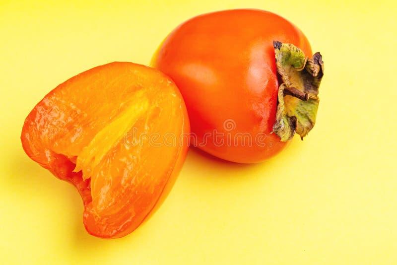 Świeża dojrzała persimmon owoc na jaskrawym żółtym tle obrazy stock