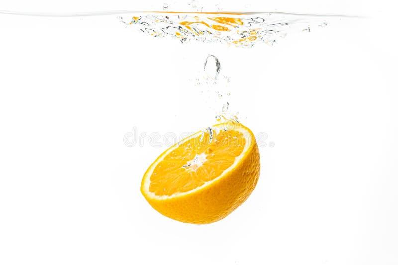 Świeża dojrzała połówka pomarańczowy owocowy słabnięcie w jasnej wodzie, odosobniona na białym tle obrazy stock