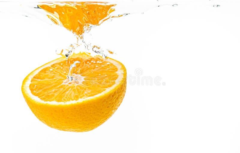 Świeża dojrzała połówka pomarańczowy owocowy słabnięcie w jasnej wodzie, odosobniona na białym tle zdjęcie royalty free