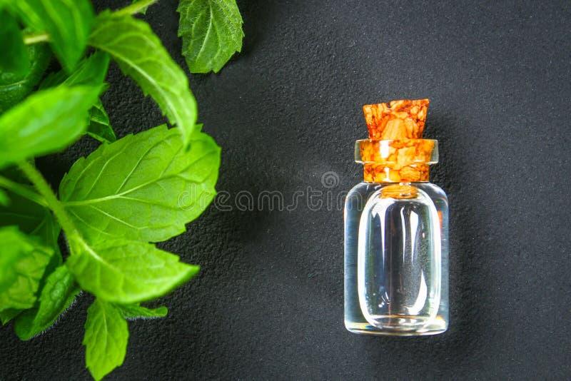 Świeża domowej roboty zielona miętówka i masło w szklanej małej butelce na szarym zmroku betonu stole Odgórny widok fotografia stock