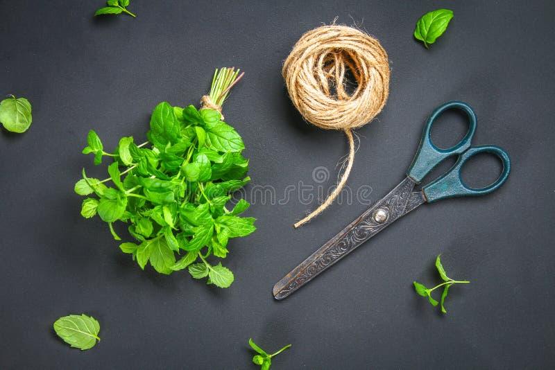 Świeża domowej roboty zielona miętówka z linową dratwą i starymi nożycami na szarym zmroku betonu stole Odgórny widok zdjęcia stock