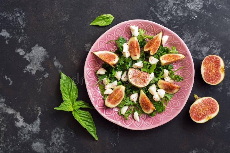 Świeża figi sałatka z mozzarellą i zielenie na ciemnym grunge drylujemy tło Odgórny widok, kopii przestrzeń zdjęcia stock