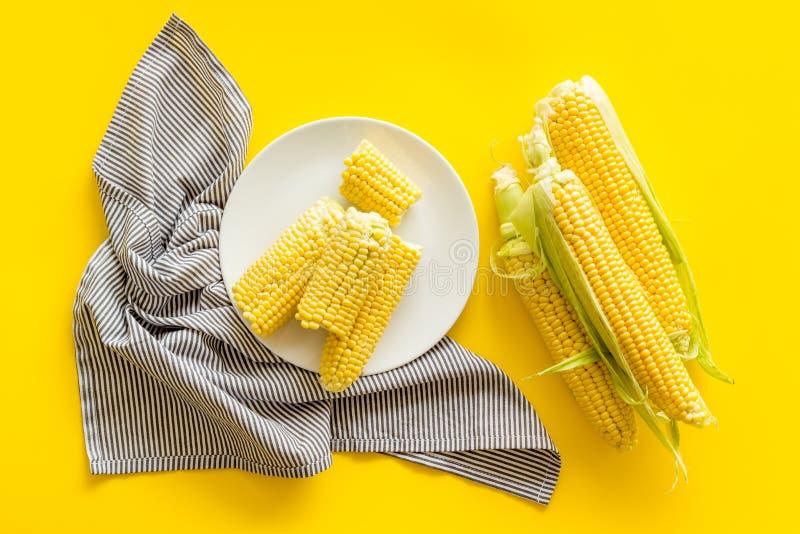 Świeża kukurudza na talerzu jako rolny jedzenie na żółtego tła odgórnym widoku zdjęcia royalty free