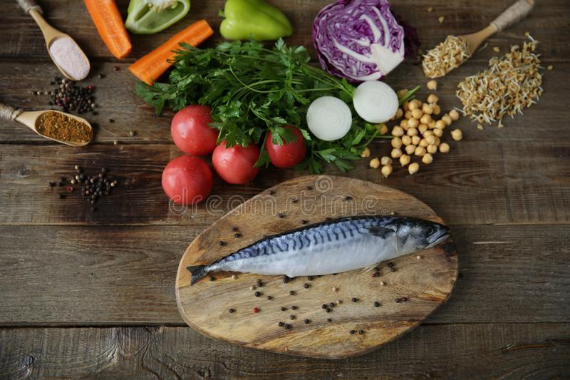 Świeża makrela odizolowywająca na drewnianej tnącej desce z warzywami, odrośniętymi fasole, ziele i pikantność, zdjęcia royalty free