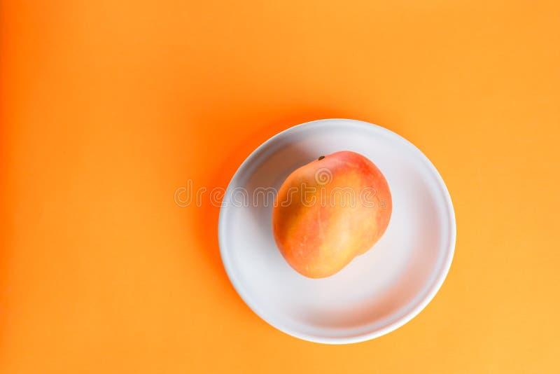 Świeża mangowa tropikalna owoc na talerzu na pomarańczowym tle obraz stock