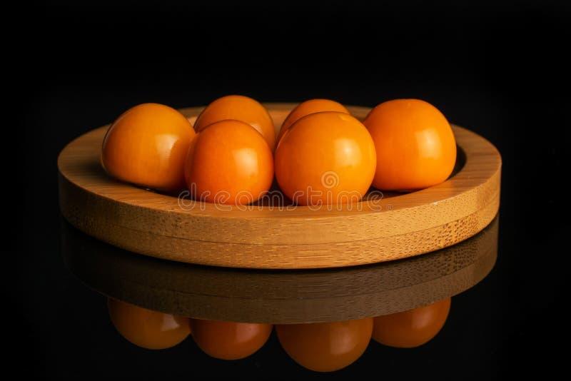 Świeża pomarańczowa pęcherzyca odizolowywająca na czarnym szkle fotografia stock