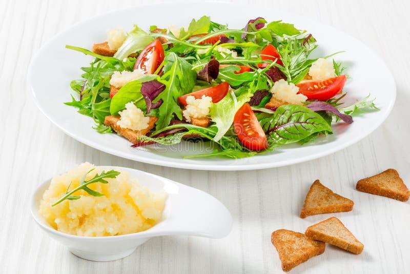 Świeża sałatka czereśniowi pomidory croutons i gromadników roe, mieszana sałata opuszcza w białym naczyniu na starym drewnianym s zdjęcie stock
