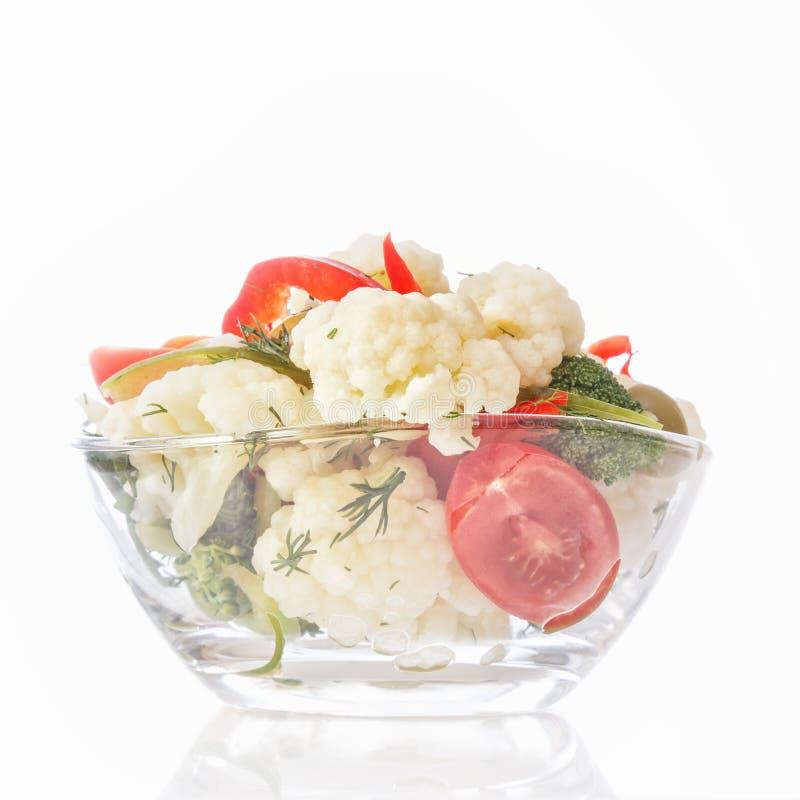Świeża sałatka kalafior z ogórkiem, brokuły, zielenie, oliwki i słodki pieprz w szklanym pucharze na białym tle, obraz royalty free