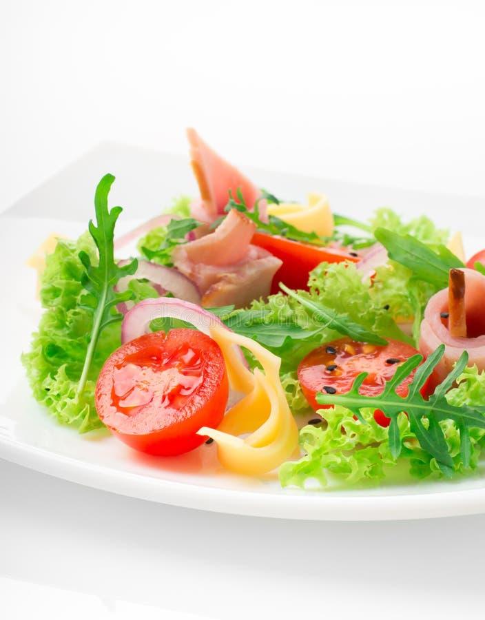 Świeża sałatka z pomidorami, arugula, serem i baleronem na białym talerzu białym tle i zdjęcia royalty free