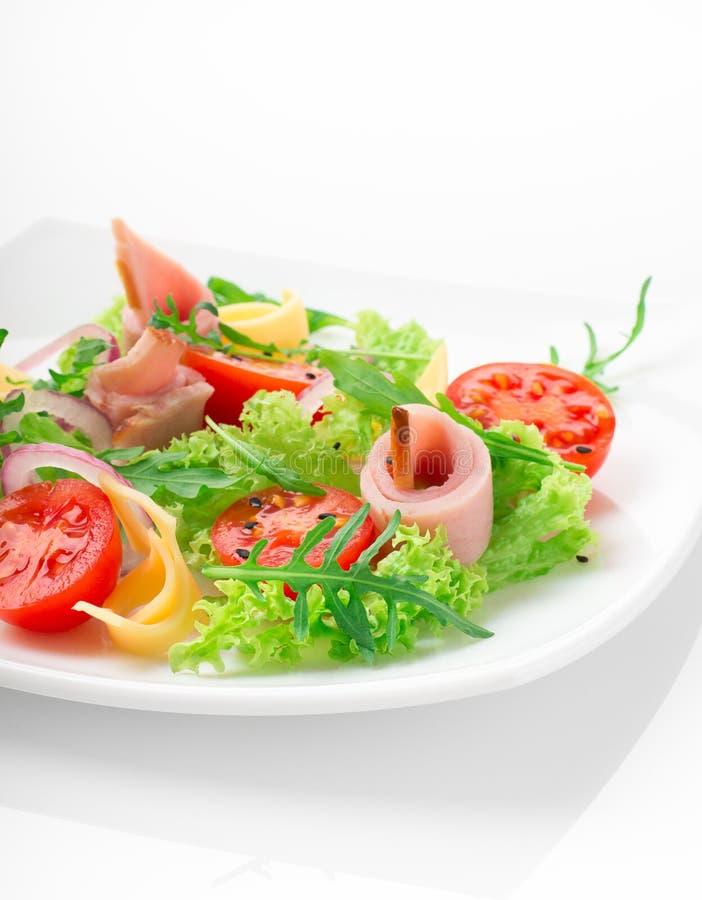 Świeża sałatka z pomidorami, arugula, serem i baleronem na białym talerzu białym tle i zdjęcie royalty free