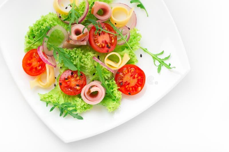 Świeża sałatka z pomidorami, arugula, serem i baleronem na białym talerzu białym tle i obraz royalty free