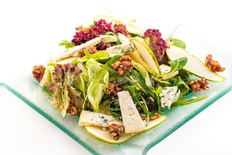 Świeża sałaty sałatka z błękitnym serem, bonkretą i karmelizującymi orzechami włoskimi na szklanym talerzu odizolowywającym na bi fotografia stock
