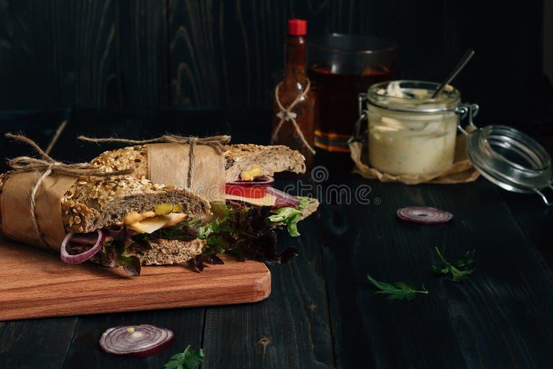 Świeża smakowita podwodna kanapka i kumberlandy na drewnianym zmroku stole fotografia stock