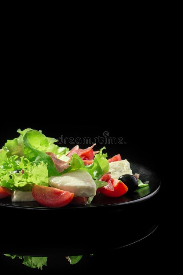 Świeża smakowita sałatka na glansowanym czarnym tle obraz stock