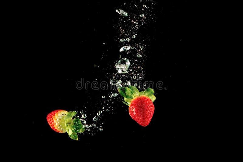 Świeża truskawka opuszczał w wodę z pluśnięciem na odosobnionym czarnym tle obraz stock