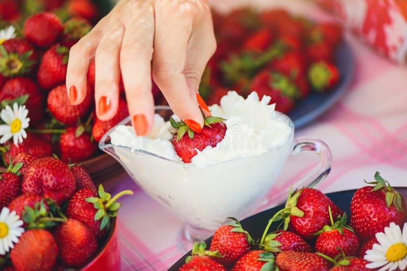Świeża truskawka z śmietanką w pucharze na stole w lato ogródzie dekoruje z chamomile kwiatami ręka bierze z lo obrazy royalty free