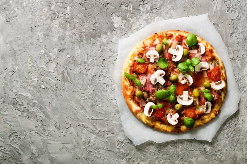 Świeża włoska pizza z pieczarkami, baleron, pomidory, ser dalej na wsparcie papierze, siwieje betonowego tło kosmos kopii zdjęcie stock