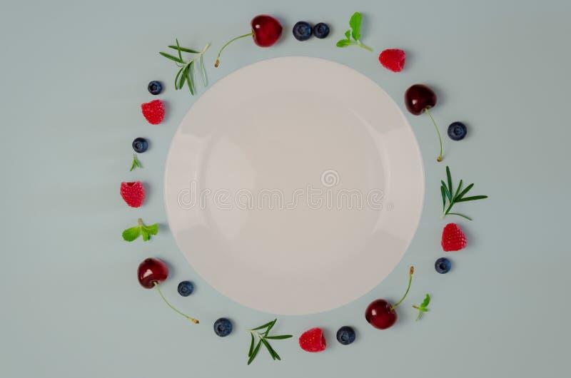 Świeża wiśnia, czarna jagoda, malinka, liść na odgórnym widoku z bielu talerzem i pastelowy błękitny koloru tło dla, mennicy i ro obraz stock