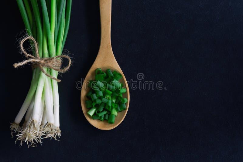Świeża wiosny cebula na czarnym granitu stole Zamyka up na siekającym c zdjęcia stock
