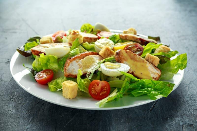 Świeża zdrowa Caesar sałatka z kurczakiem, jajeczną przepiórką, pomidorami, serem i Croutons w białym talerzu, zdjęcia stock