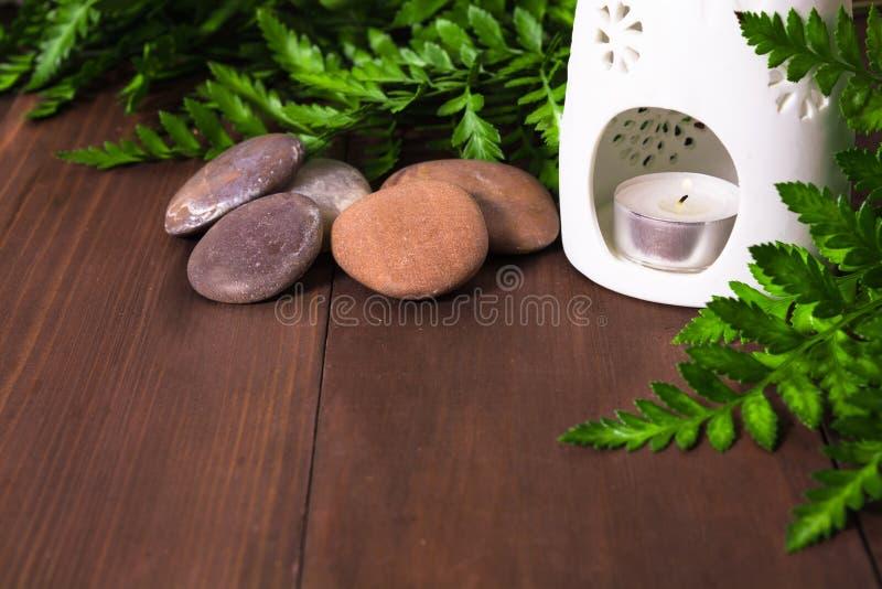 Świeża zielona paproć, świeczka w aromat lampie i kamienie dla zdroju massag, obrazy royalty free