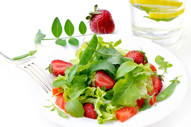 Świeża zielona sałatka z dojrzałymi pomidorami, strąkami zieleni grochy i plasterkami truskawka, zdjęcie royalty free