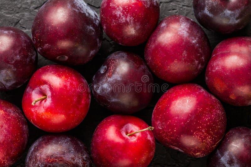 Świeże śliwki na zmroku drylują tło, makro- zdrowy owoc lato zdjęcia stock