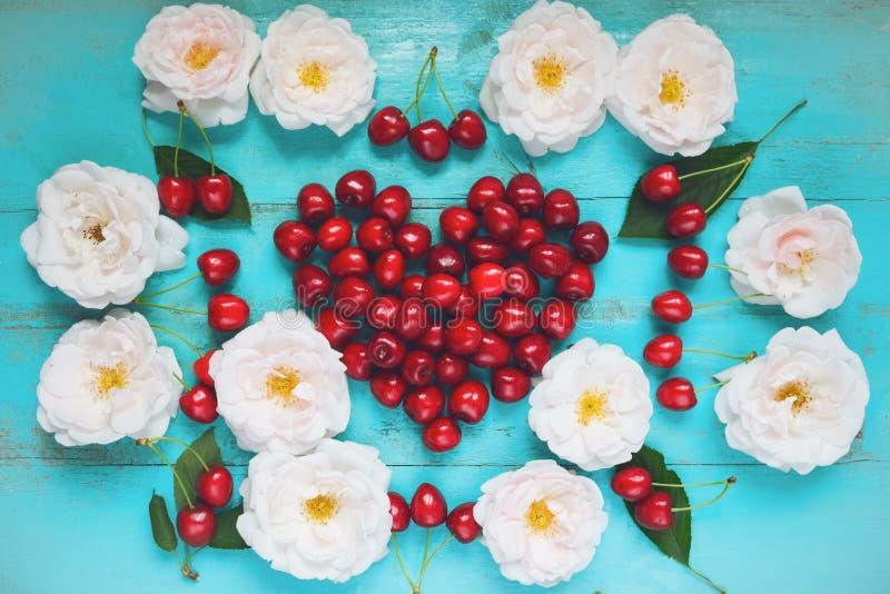 Świeże białe róże z wodnymi kroplami, czerwona wiśnia w kształcie serce na starym malującym drewnianym stole jako jaskrawy koloro zdjęcia stock
