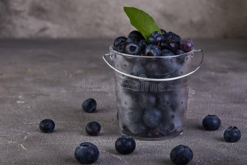 Świeże czarne jagody w przejrzystym wiadrze na szarości betonują zdjęcia royalty free
