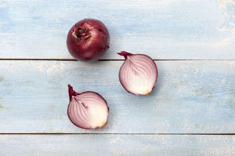 Świeże czerwone cebule na błękitnym drewnianym tle zdjęcie stock