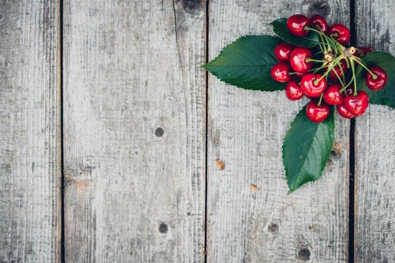 Świeże czerwone wiśnie na starym drewnianym stole z zielonymi liśćmi, wieśniaka styl zdjęcie royalty free