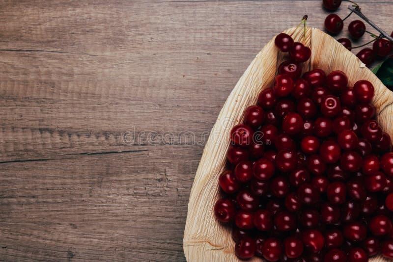 Świeże czerwone wiśnie w drewnianym talerzu na drewnianym stole Drewniany talerz na drewnianym tle obok go jest czereśniowa gałąź obraz royalty free