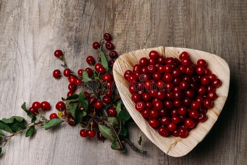Świeże czerwone wiśnie w drewnianym talerzu na drewnianym stole Drewniany talerz na drewnianym tle obok go jest czereśniowa gałąź zdjęcia royalty free