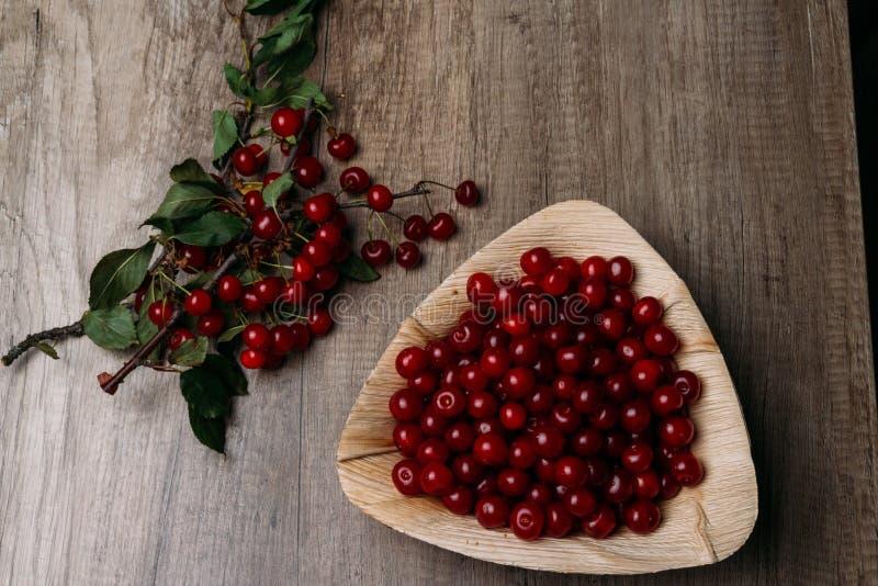 Świeże czerwone wiśnie w drewnianym talerzu na drewnianym stole Drewniany talerz na drewnianym tle obok go jest czereśniowa gałąź zdjęcia stock