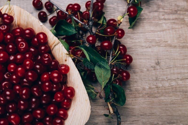 Świeże czerwone wiśnie w drewnianym talerzu na drewnianym stole Drewniany talerz na drewnianym tle obok go jest czereśniowa gałąź obraz stock