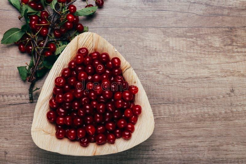 Świeże czerwone wiśnie w drewnianym talerzu na drewnianym stole Drewniany talerz na drewnianym tle obok go jest czereśniowa gałąź zdjęcie royalty free
