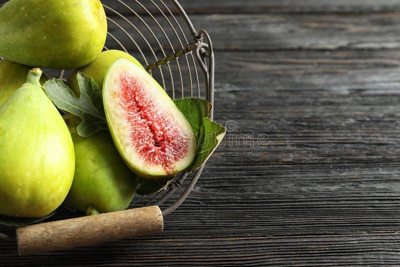 Świeże dojrzałe figi w koszu na drewnianym stole, odgórny widok fotografia royalty free