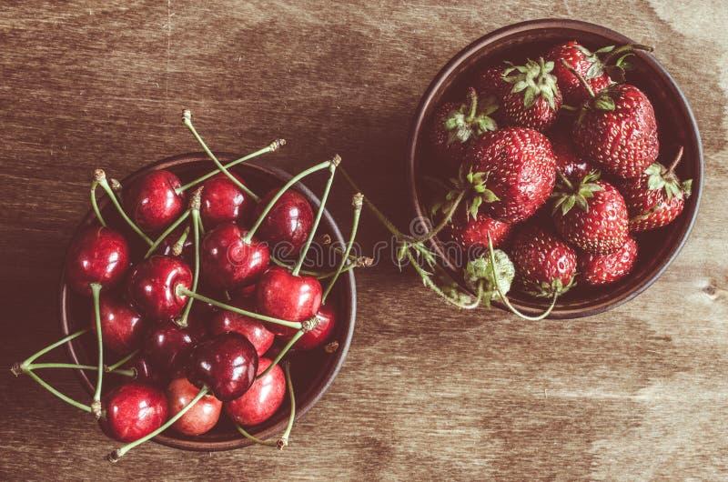 Świeże dojrzałe organicznie wiśnie i truskawka na drewnianym tle Rocznika wieśniaka styl i koloru zabarwiać zdjęcie stock